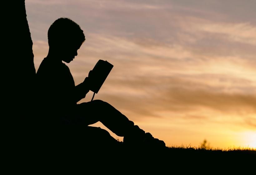 Bambino legge al tramonto